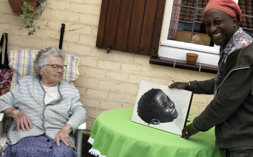Eric Baranyanka, right, and his foster mother, Emma Monsaert, look at a photo of Eric as a young boy in Lembeek, Belgium.