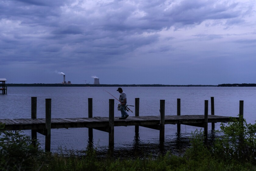 A fisherman walks along a dock on the St. Johns River as a coal-fired power plant stands in the background, in Palatka, Fla.