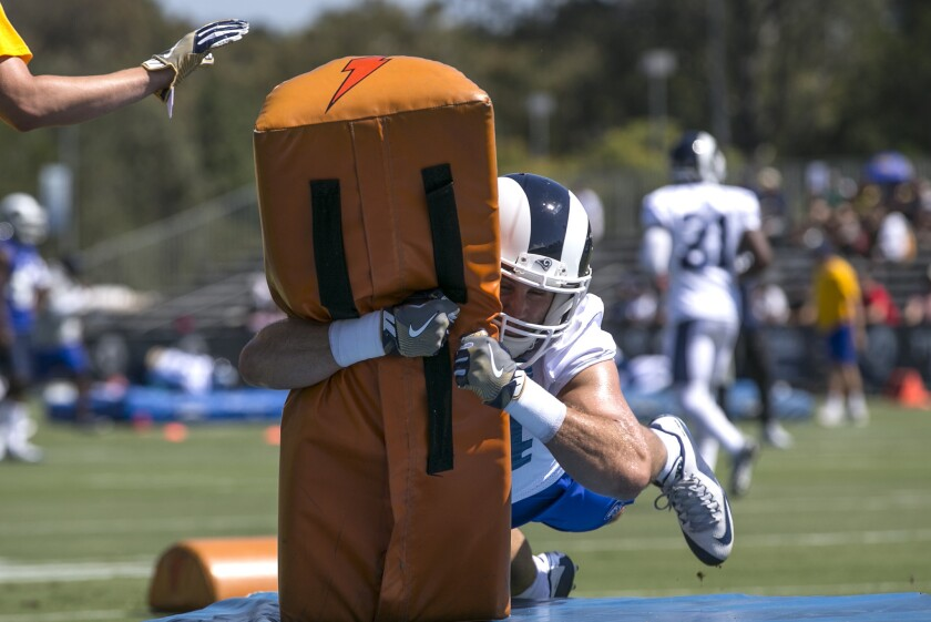 Linebacker Bryce Hager dives into a tackling dummy during special teams drills at Rams training camp.