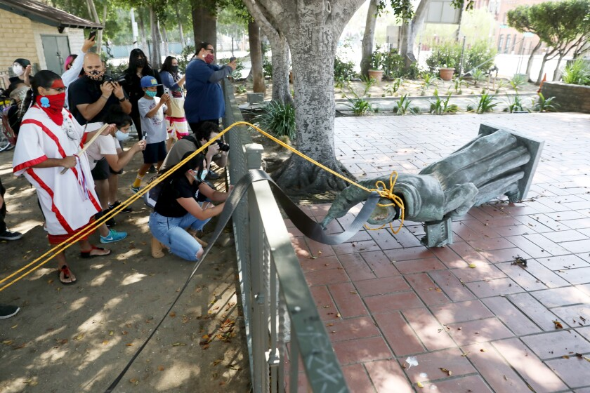 Activists topple the statue of Father Junipero Serra at Father Serra Park in Pueblo Amigo on Saturday.
