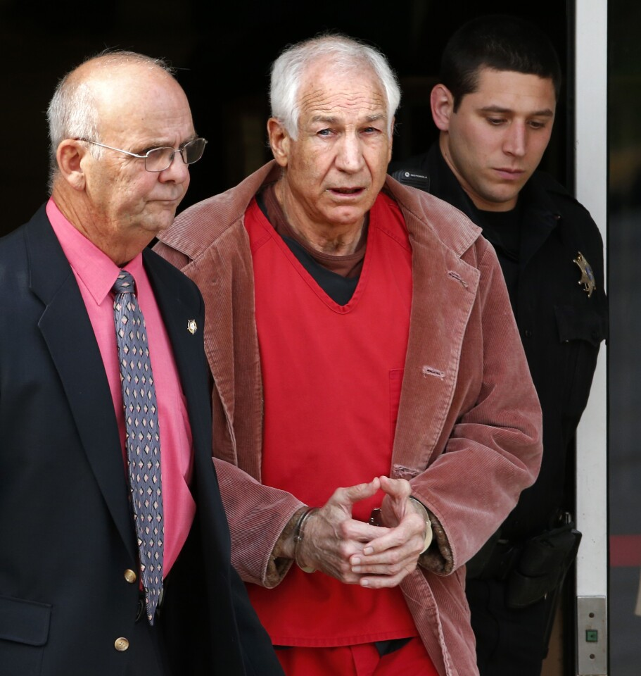 Former Penn State University assistant football coach Jerry Sandusky, center, leaves the Centre County Courthouse escorted by Centre County Sheriff Denny Nau, left, after attending a hearing about his appeal in Bellefonte, Pa., Thursday, Oct. 29, 2015. The hearing Thursday concerns whether Sandusky's lawyers can be allowed to subpoena witnesses and get access to emails between prosecutors and judges.