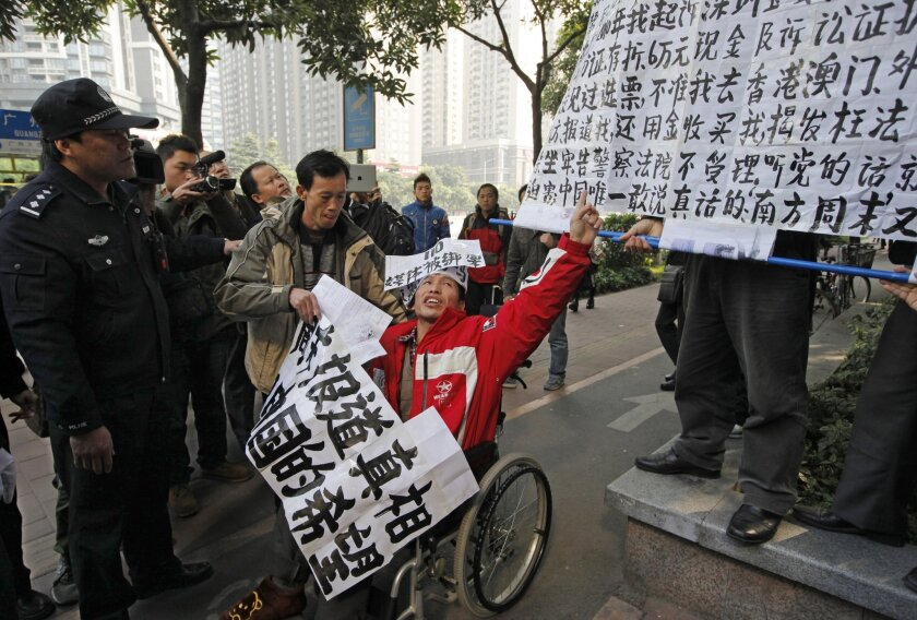 FILE - In this Jan. 10, 2013 file photo, a policeman stands near a supporter, center in wheelchair, of the Southern Weekly during a protest before being taken away by police near the Southern Weekly headquarters in Guangzhou, Guangdong province, China. A court sentenced Chinese activist Yang Maodong - better known by his penname Guo Feixiong - to six years in prison Friday, Nov. 27, 2015, in what his lawyer described as an unfair trial with an extra criminal charge added at the last minute. Yang helped organize demonstrations and spoke in support of the editorial staff at Southern Weekly after its journalists complained of censorship. (AP Photo/Vincent Yu, File)
