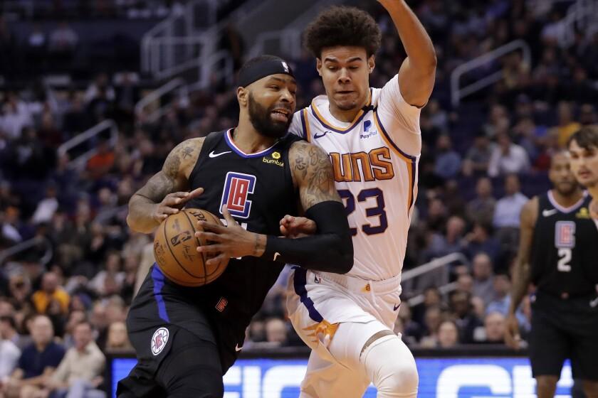 Clippers forward Marcus Morris drives as Phoenix Suns forward Cameron Johnson defends Feb. 26.