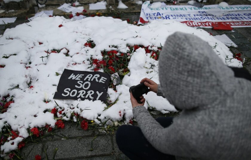 A visitor takes pictures of snow covered flowers and messages left at the site of the Jan. 12 explosion, in the historic Sultanahmet district in Istanbul, Monday, Jan. 18, 2016. A suicide bomber set off an explosion near a group of German tourists just steps away from the landmark Blue Mosque, killing 10 of them. (AP Photo/Emrah Gurel)