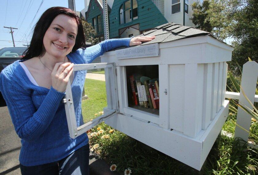 Megan Rozek muestra el contendió de la mini biblioteca gratuita frente a su casa en Carlsbad.