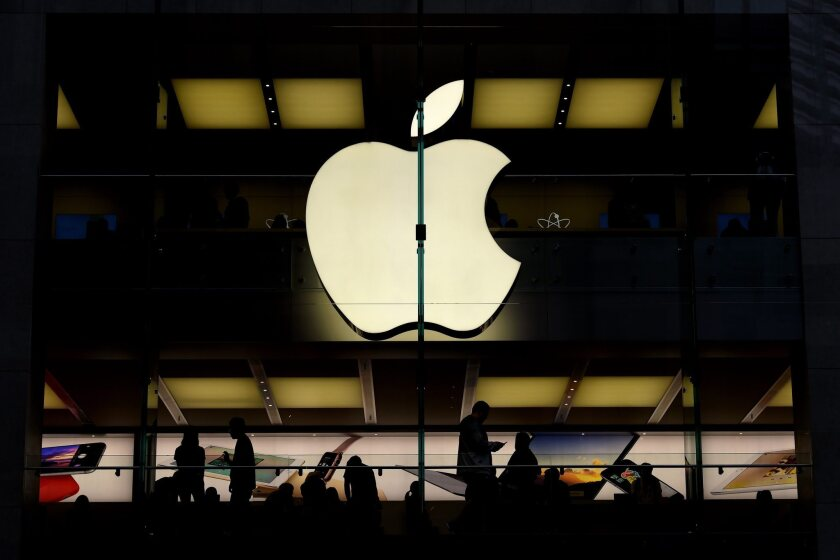 Customers are silhouetted inside of an Apple store in Sydney, Australia.