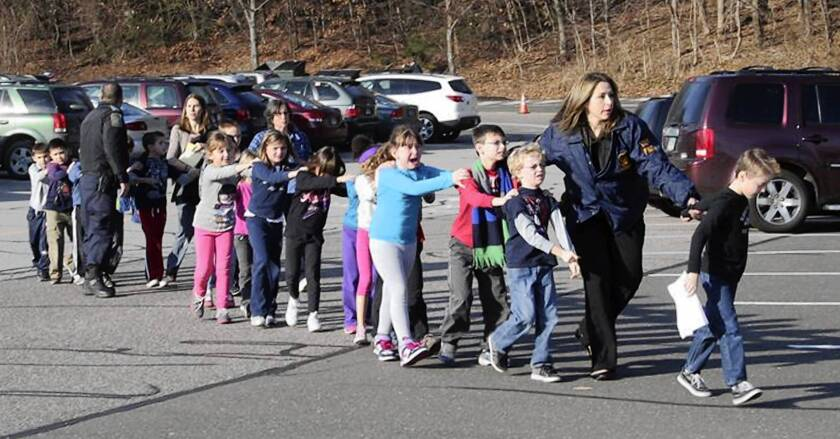 State police lead children from Sandy Hook Elementary School in Newtown, Conn., after the shooting. Students had huddled in closets and corners as the carnage unfolded.