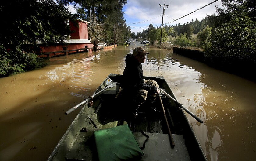 Bruce MacDonnell paddles over a flooded road in Guerneville on Wednesday after the Russian River crested.
