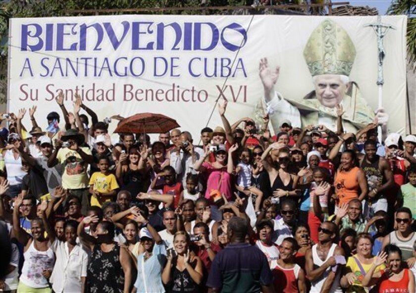 Cubans wave and cheer as Pope Benedict XVI, not seen, is being driven along the streets of Santiago de Cuba, Cuba, Monday March 26, 2012.(AP Photo/Desmond Boylan,Pool)