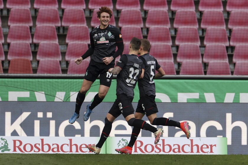 Bremen's Joshua Sargent, left, celebrates scoring with teammates Marco Friedl and Ludwig Augustinsson, right, during the German Bundesliga soccer match between 1. FC Cologne and Werder Bremen in Cologne, Germany, Sunday, March 7, 2021. (Rolf Vennenbernd/dpa via AP)