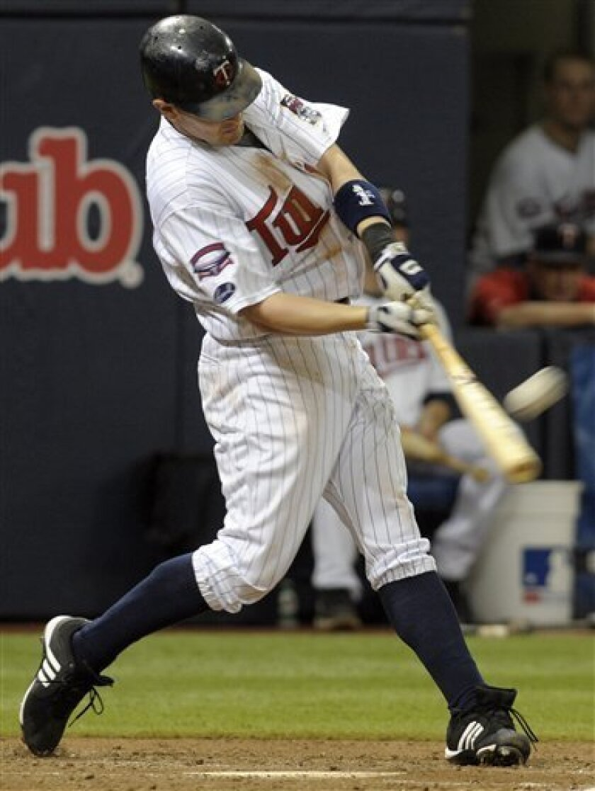 Minnesota Twins' Brendan Harris hits a two-run home run off Chicago White Sox pitcher Mark Buehrle during the fourth inning of a baseball game Sunday, July 12, 2009, in Minneapolis.(AP Photo/Tom Olmscheid)