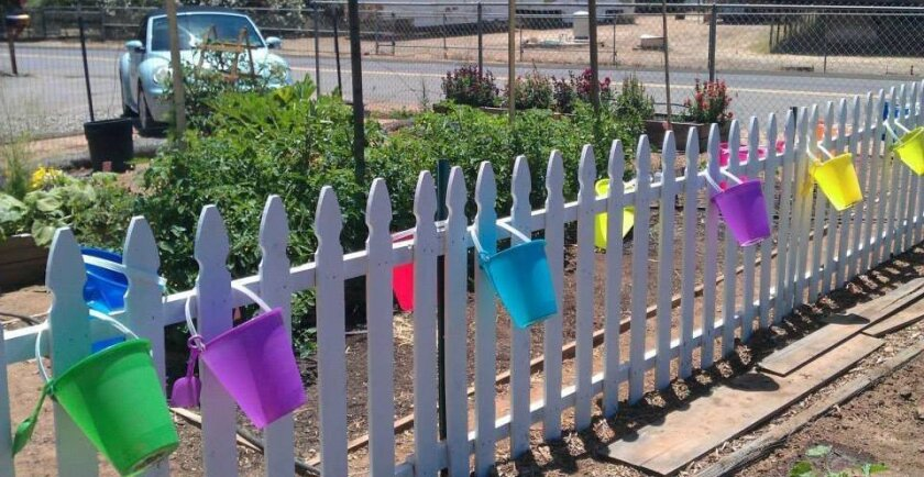 Pails dangle from the white fence around the Ryan Carter Memorial Children's Garden in Lakeside.