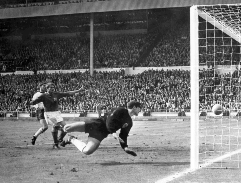 FILE - In this July 30, 1966 file photo, England's Roger Hunt, center, raises his arms as Geoff Hurst scores England's third goal past German goalkeeper Hans Tilkowski, right, during the Football World Cup Final at Wembley Stadium, London. Roger Hunt, a striker in the only England team to win the World Cup and one of Liverpool's most prolific scorers, has died. He was 83. Liverpool, where Hunt spent most of his playing career, said he died on Monday Sept. 27, 2021, after a long illness. (AP Photo/Bippa, File)