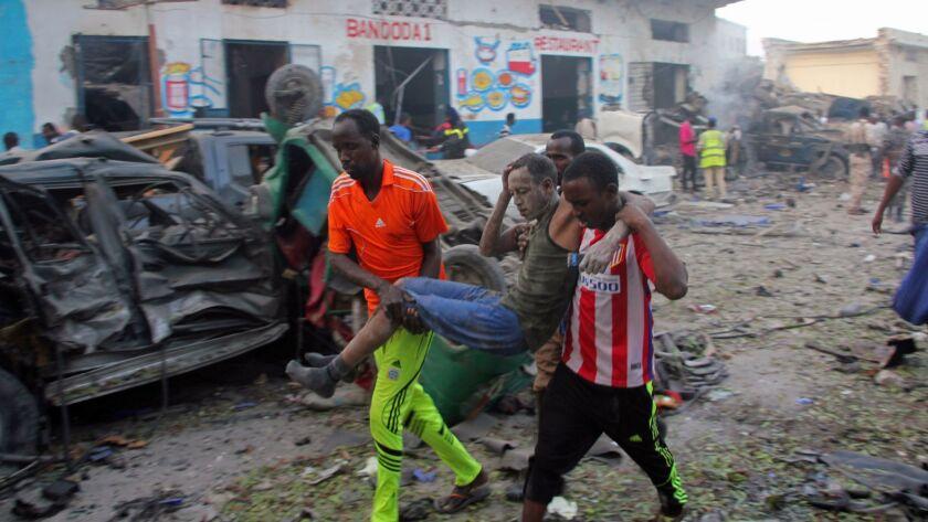 Somalis carry away a man injured after a car bomb was detonated in Mogadishu, Somalia Saturday, Oct