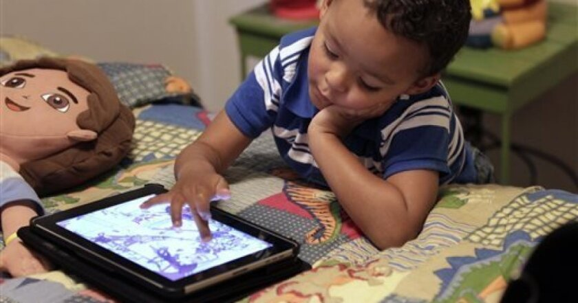 In this Friday, Oct. 21, 2011 file photo, Frankie Thevenot, 3, plays with an iPad in his bedroom at his home in Metairie, La. As of Wednesday, Aug. 7, 2013, the Campaign for a Commercial-Free Childhood, a Boston-based group, is urging federal investigators to examine the marketing practices of Fisher-Price's and Open Solution's mobile apps. It's the campaign's first complaint against the mobile app industry as part of its broader push to hold accountable businesses that market technology.