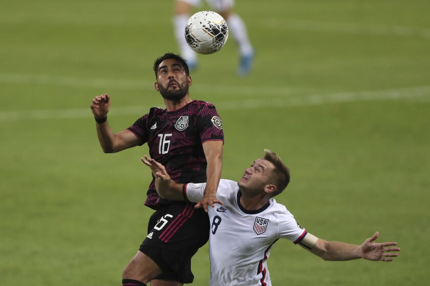 Mexico's Jose Esquivel heads the ball while challenged by the United States' Djordje Mihailovic