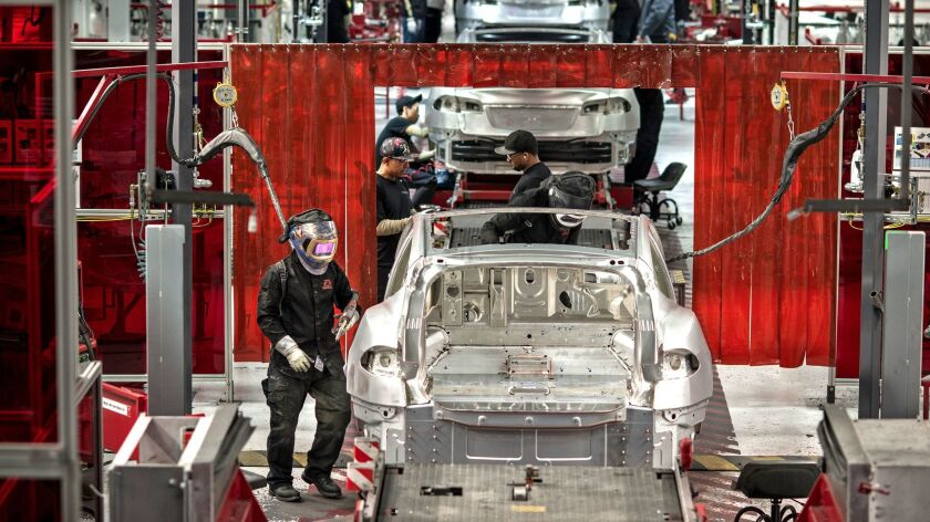 Scenes at the Tesla car factory include welders assembling various components.