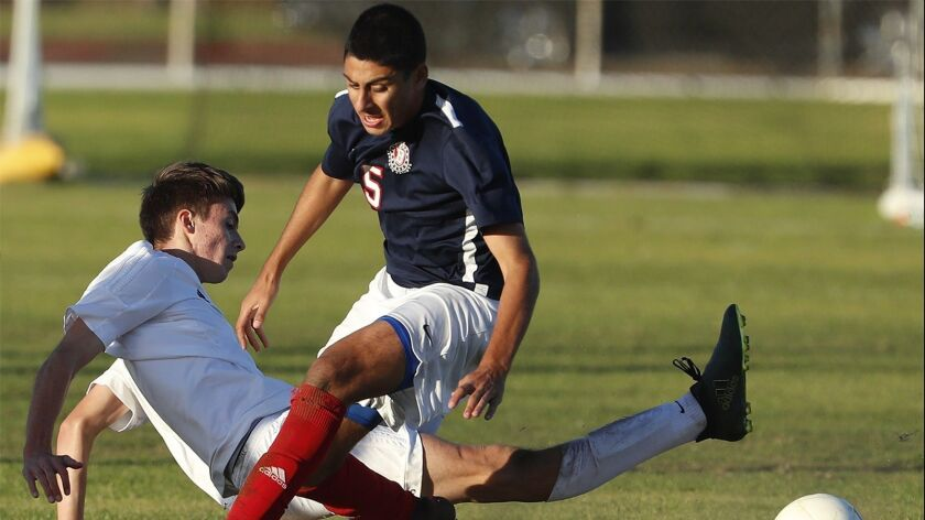 Corona del Mar's Niko Urban goes to the ground to advance the ball past Beckman's Kian Aminloo durin