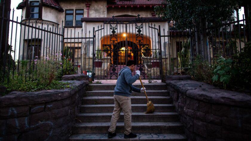 LOS ANGELES, CALIF. - MAY 16: Hildner Coronado Atjun sweeps the front stairs of Casa Libre on Thursd