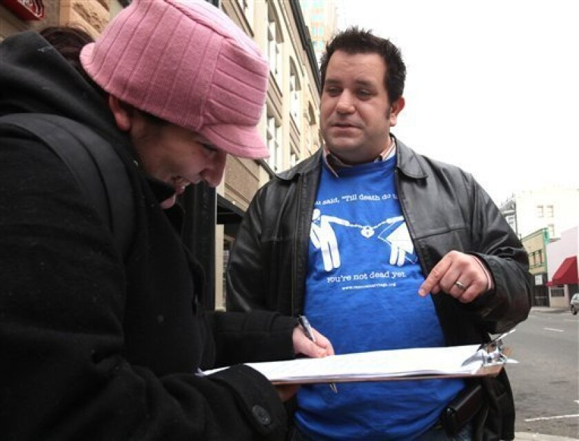 In this photo taken Saturday, Nov. 21, 2009, John Marcotte discusses his proposed ballot initiative to ban divorce as Cynthia Keagy, left, signs his petition to get measure on the ballot, in Sacramento, Calif. Marcotte is using the state's voter initiative process to make a satirical statement abou