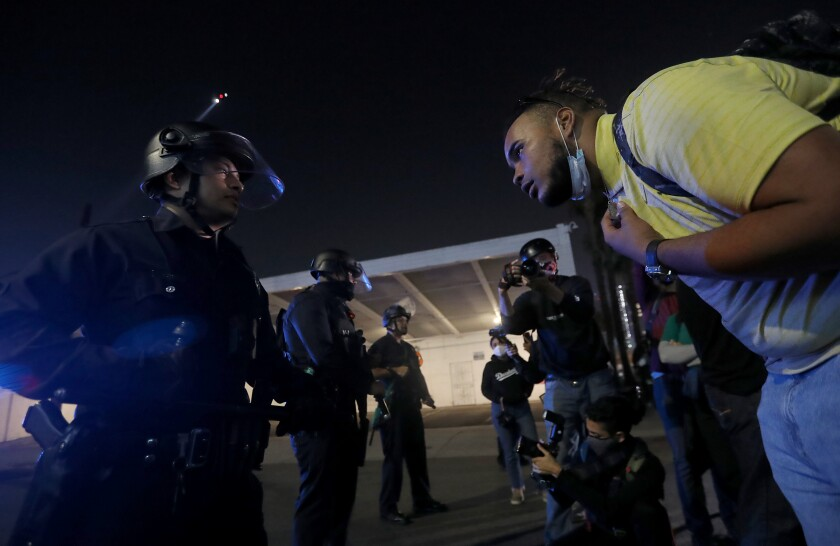 A protester confronts an LAPD officer in downtown Los Angeles on election night.