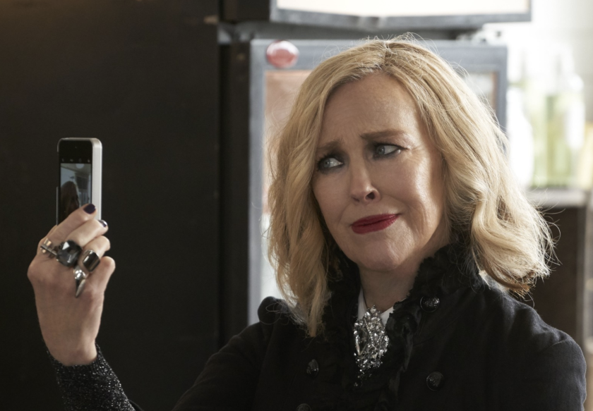Catherine O'Hara looks at herself on her cell phone