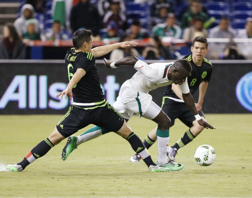 Mexico's Jorge Torres Nilo, left, and Hirving Lozano (8) battle for the ball with Senegal's Dame Gueye during the second half of a soccer match at Marlins Park, Wednesday, Feb. 10, 2016, in Miami. Mexico defeated Senegal 2-0. (AP Photo/Wilfredo Lee)