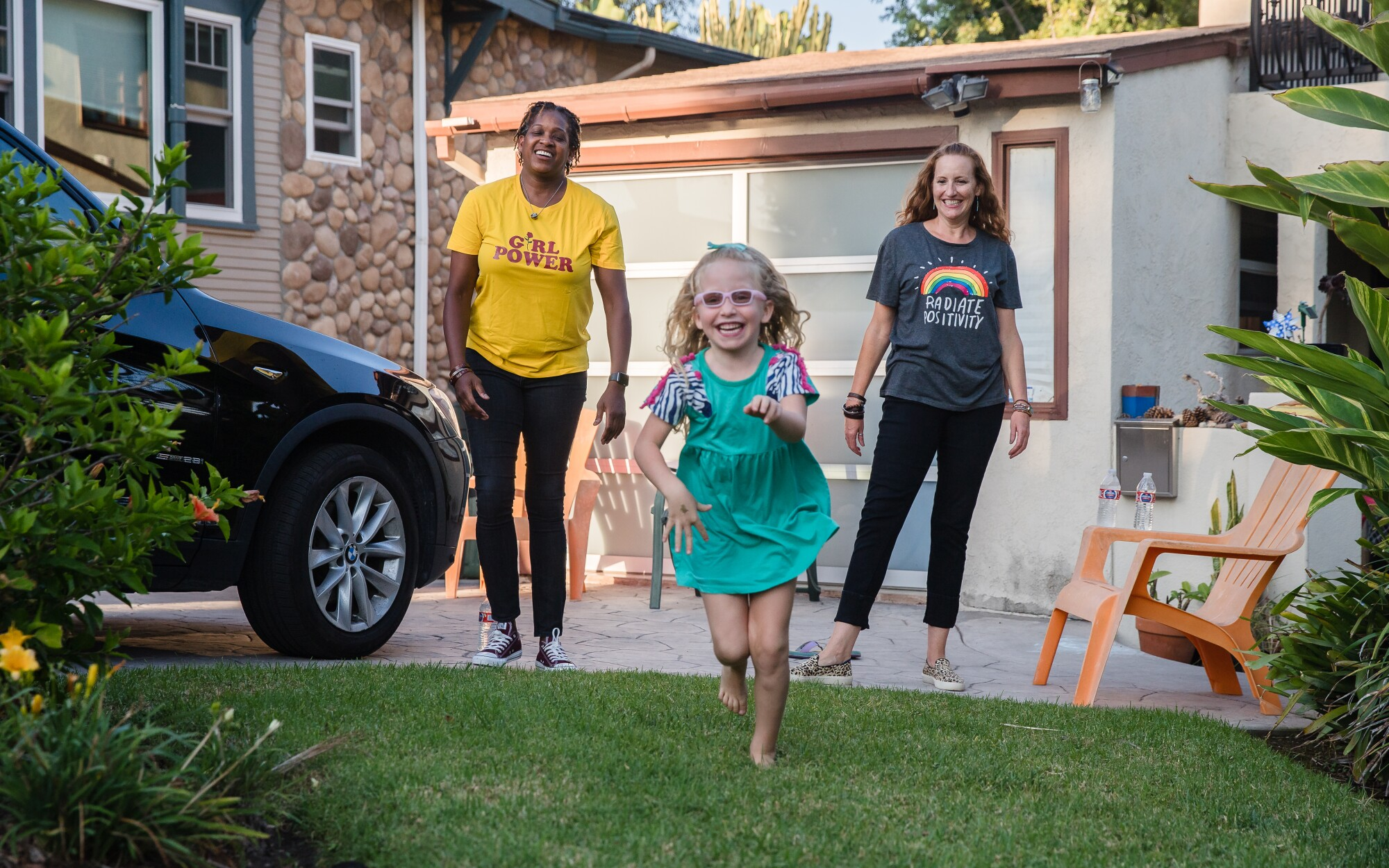 Jyla Berry-Woods (center), plays in the front yard with her moms, Jualeah Woods (left) and Jennifer Berry (right).