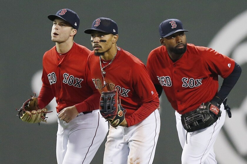"FILE - In this Friday, April, 12, 2019 file photo, Boston Red Sox's Andrew Benintendi, left, Mookie Betts, center, and Jackie Bradley Jr. run in after defeating the Baltimore Orioles during a baseball game in Boston. When the Boston Red Sox traded Mookie Betts to the Los Angeles Dodgers on the eve of spring training, they broke up the ""Killer B's"" who patrolled the Fenway outfield and led the team to a World Series championship in 2018. Together, Betts, Jackie Bradley Jr. and Andrew Benintendi formed one of the best outfields in baseball. (AP Photo/Michael Dwyer, File)"