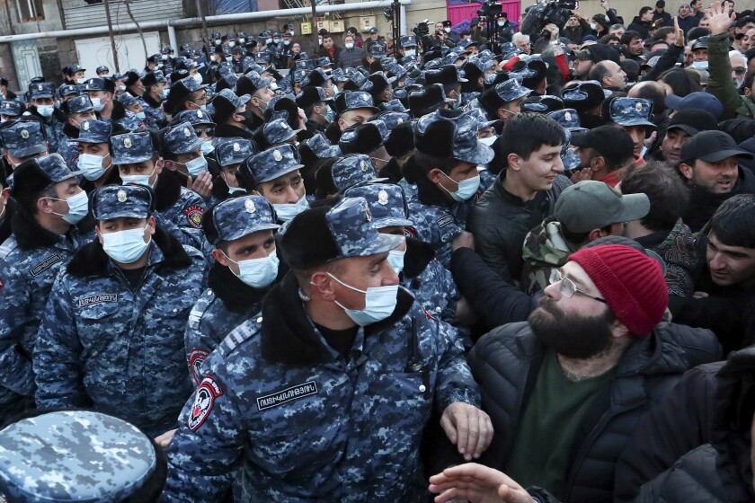 Police wearing face masks to protect against coronavirus, block opposition demonstrators during a rally to pressure Armenian Prime Minister Nikol Pashinyan to resign in Yerevan, Armenia, Tuesday, March 9, 2021. Thousands of opposition supporters blockaded the Armenian parliament building and engaged in occasional scuffles with police on Tuesday to press a demand for the country's prime minister to step down. (Stepan Poghosyan/PHOTOLURE via AP)