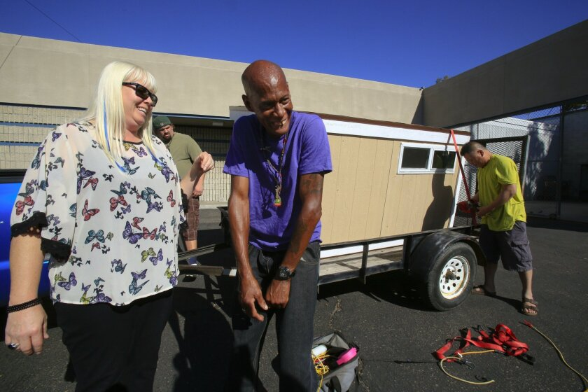 "Lisa Kogan (left) and Michael ""Redd"" Clark share a laugh after his 4-foot by 8-foot home was released from the San Diego Police Department's impound lot. The tiny home was impounded when he was arrested Dec. 15 for living out of the home on public property."
