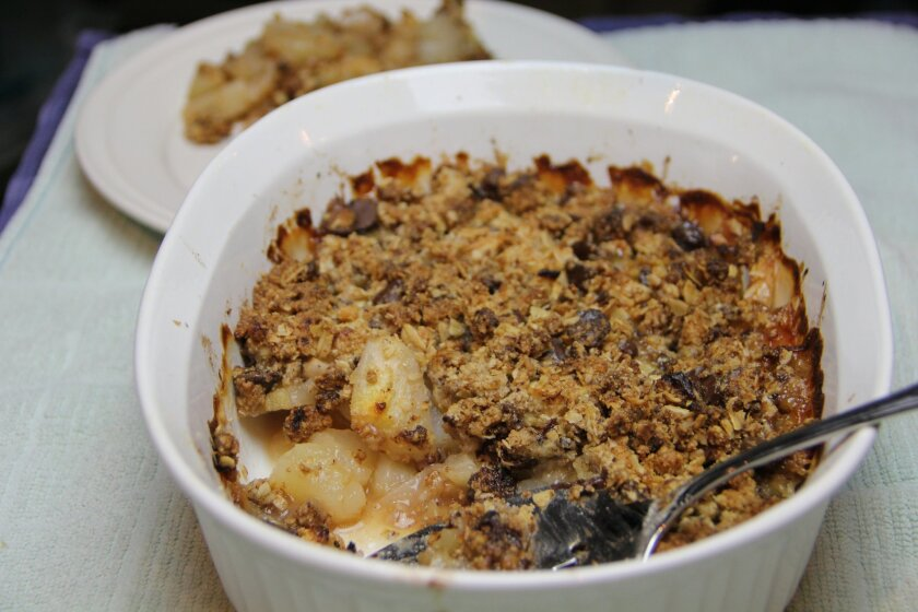 This May 25, 2016 photo shows a pear and dark chocolate crumble in Coronado, Calif. The dish turns almond flour and oats in a tasty topping that isn't loaded with empty calories, and a tiny splash of almond extract brilliantly tricks the palate into thinking this dessert is sweeter than it is. (AP