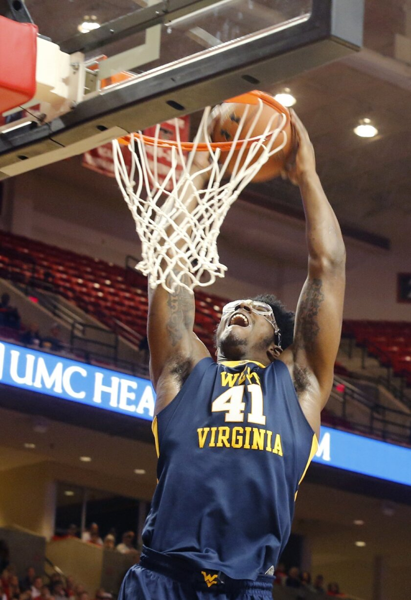 West Virginia's Devin Williams slam dunks in the first half of an NCAA college basketball game Saturday, Jan. 23, 2016, in Lubbock, Texas. (Mark Rogers/Lubbock Avalanche-Journal via AP) ALL LOCAL TELEVISION OUT; MANDATORY CREDIT