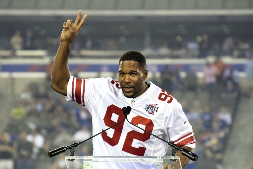FILE - In this Sept. 18, 2017, file photo, former New York Giants player Michael Strahan gestures during a halftime ceremony of an NFL football game between the Giants and the Detroit Lions in East Rutherford, N.J. The Giants are going to retire the No. 92 jersey of Hall of Fame defensive end Michael Strahan this season. The ceremony will take place on Nov. 28 at MetLife Stadium at a game against the Philadelphia Eagles. (AP Photo/Bill Kostroun, File)