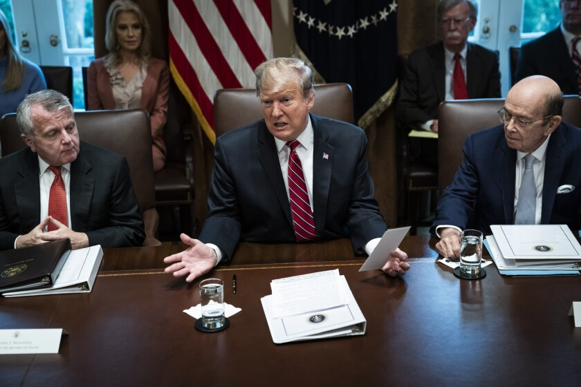 President Donald Trump, flanked by Deputy Secretary of State John Sullivan, left, and Secretary of Commerce Wilbur Ross, speaks during a Cabinet meeting at the White House on Feb. 12, 2019.