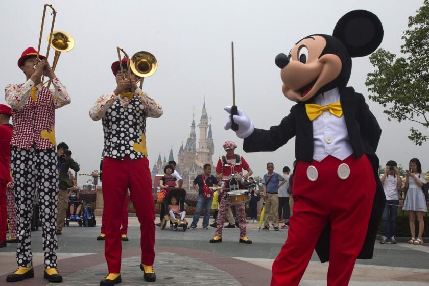 """Mickey Mouse entretiene a los visitantes el día de la apertura del Disney Resort en Shangai, China, el jueves 16 de junio de 2016. Walt Disney Co. inauguró el jueves su primer parque temático en la China continental y prometió una experiencia """"característicamente china"""" en las instalaciones, donde habrá una casa de té y muñecas de Minnie Mouse con vestidos tradicionales qipao, además de su característico castillo y un hotel de Toy Story. (AP Foto/Ng Han Guan)"""