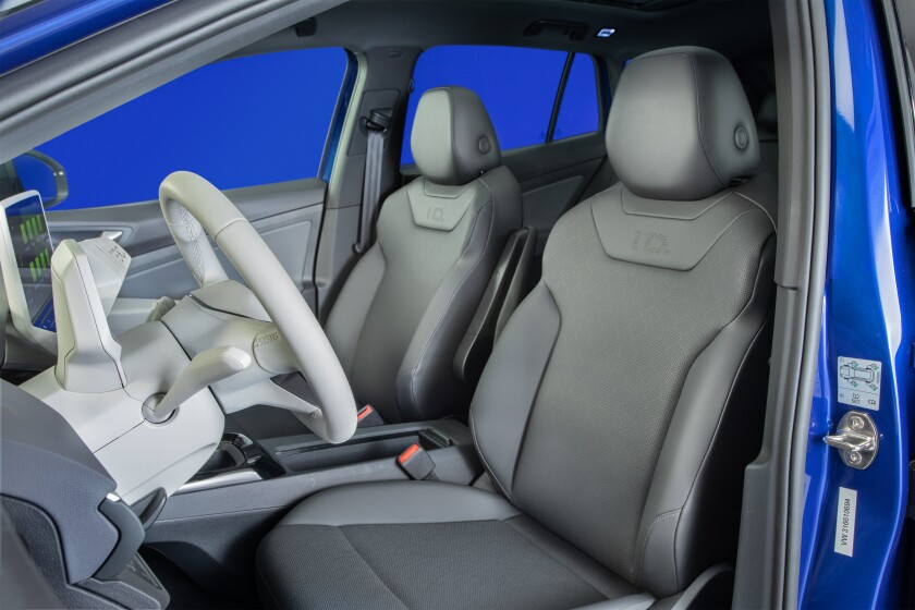 The white interior of the Volkswagen ID.4 showing front seats and steering wheel