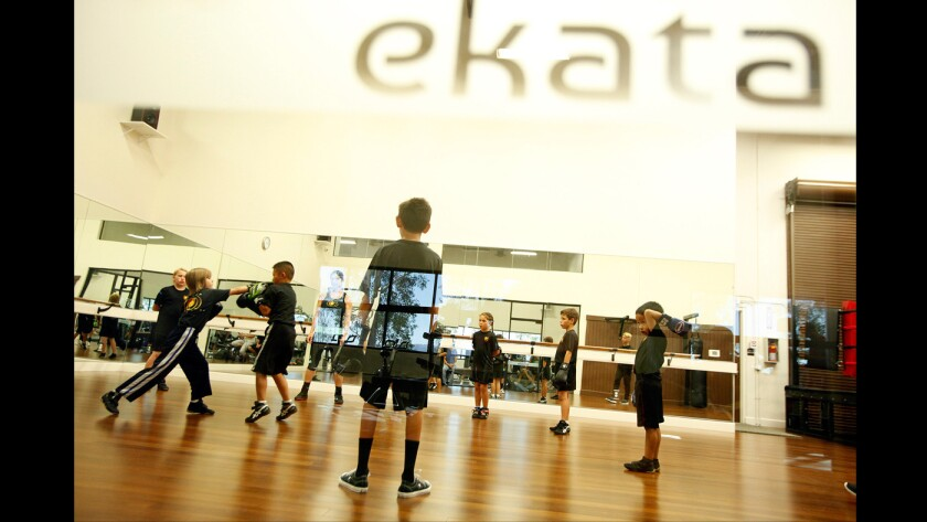 Youngsters participate in savate, a French-style kickboxing class, at the Ekata fitness center in Valencia.