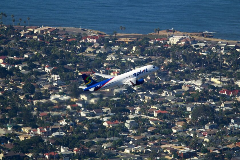 A Spirit Airlines jet takes off from San Diego International Airport over Point Loma.