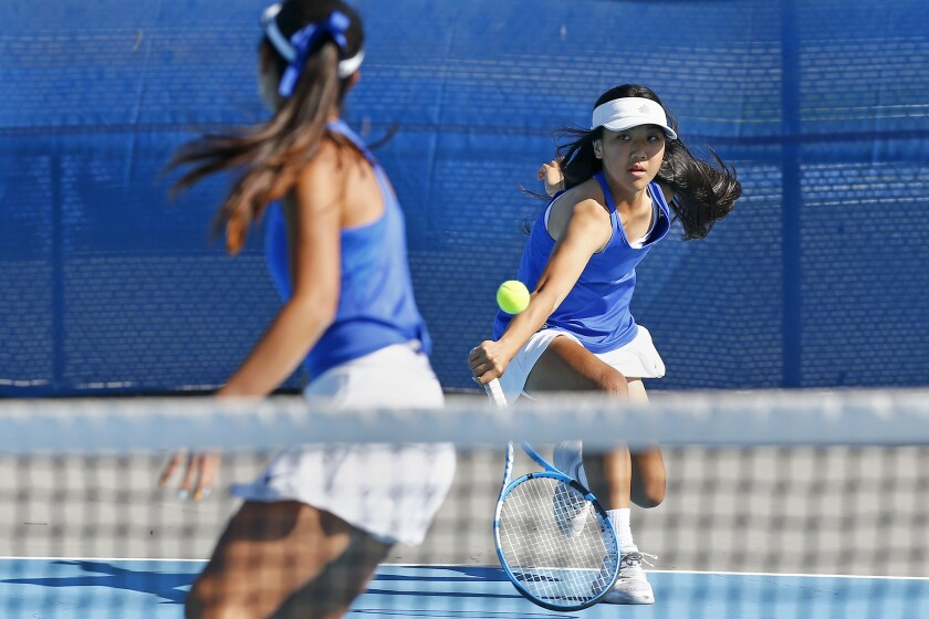 Fountain Valley No. 1 doubles partners Emily Tran, right, and Kaylee Tran, left, return a shot against Villa Park on Friday.