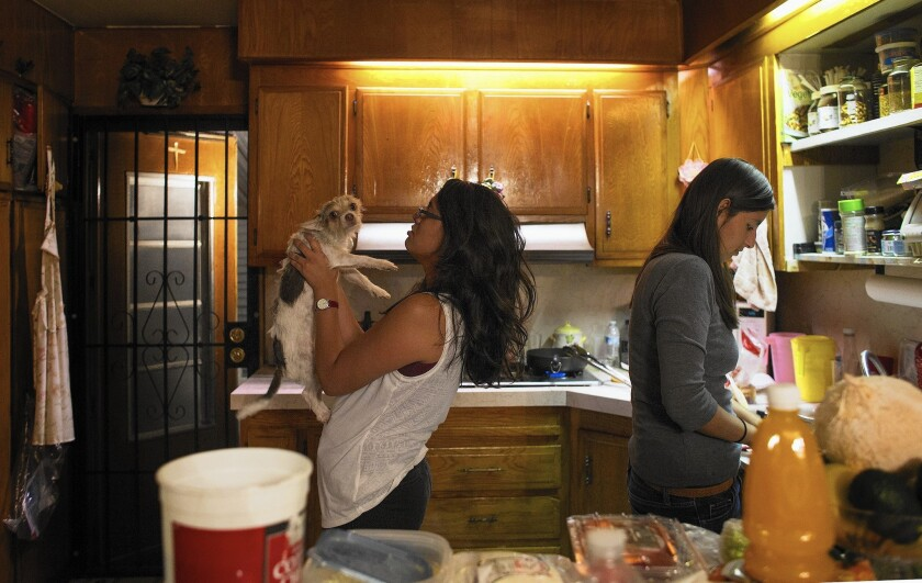 Lilian, 23, left, and her sister Norma, 21, fix dinner at their family's Covina home. They are hesitant to sign up for Obamacare because their parents are immigrants who are not citizens.