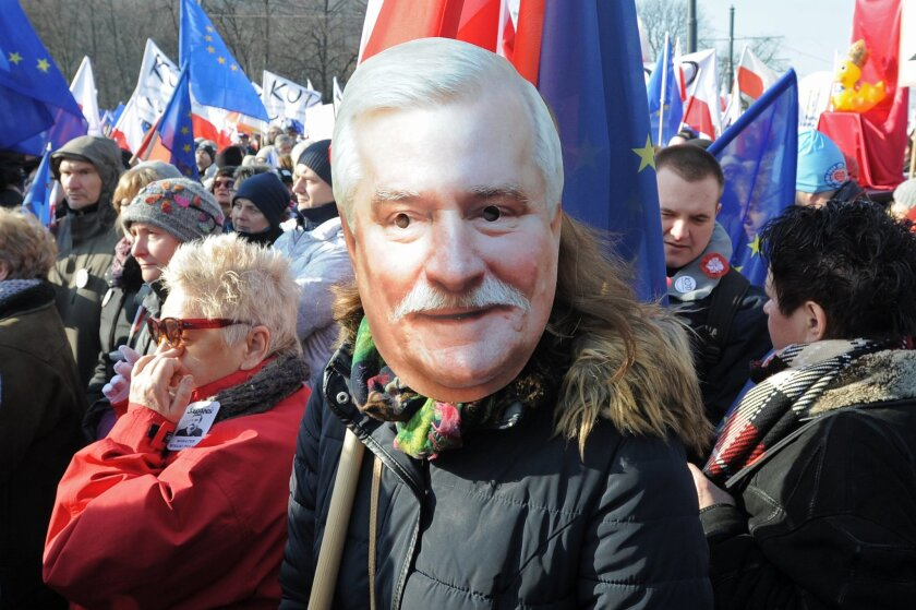 "A protester wears a mask showing former president Lech Walesa during an anti government protest, in Warsaw, Poland, Saturday, Feb. 27, 2016. Thousands of Poles were chanting ""We will defend democracy!"" and ""Lech Walesa!"" rallied to protest moves by Poland's three-month-old conservative government that they say undermine freedoms and the constitution. (AP Photo/Alik Keplicz)"