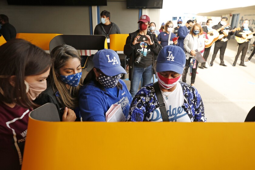 Roxanna Jacinto helps her mother, Salvadora Martir, 73, right, as she votes for the first time at Dodger Stadium.