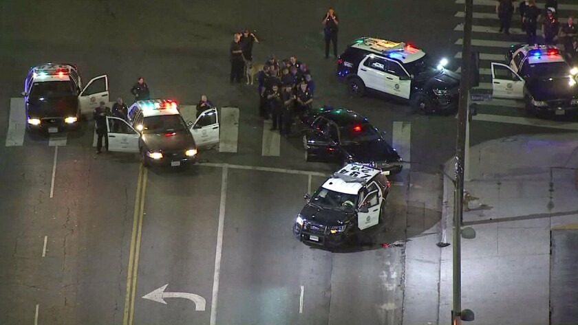 Officers respond to the scene where one of three stolen Los Angeles police cruisers crashed in South L.A. Three teens were detained after crashing two of the vehicles following two separate, brief pursuits Wednesday night, officials said.