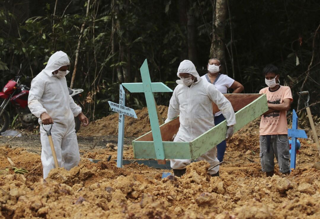 Funeral workers in protective gear prepare a grave for a COVID-19 victim at the Nossa Senhora Aparecida cemetery in Brazil.