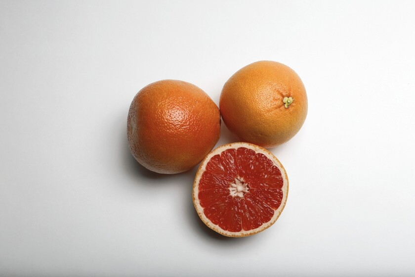 A still life of whole and cut grapefruit on a white background