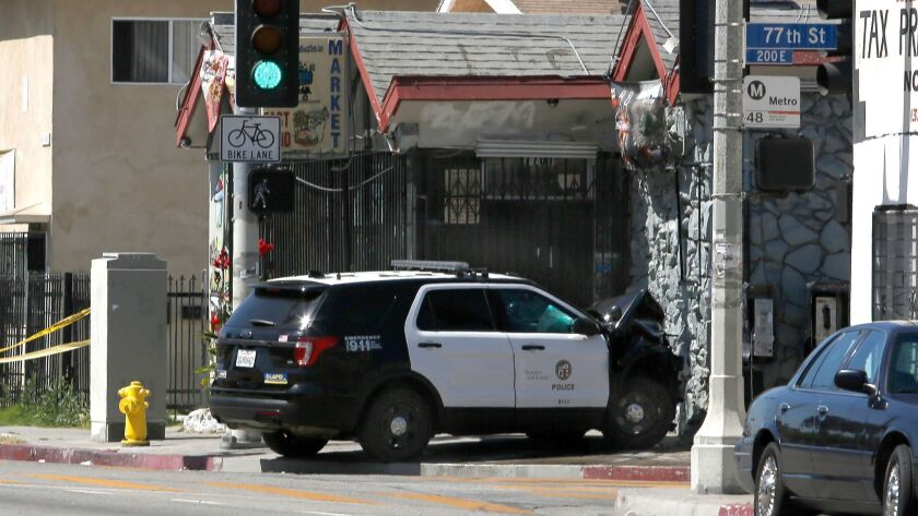 A police SUV rests Thursday where it crashed near the intersection of 77th and San Pedro streets in Los Angeles.