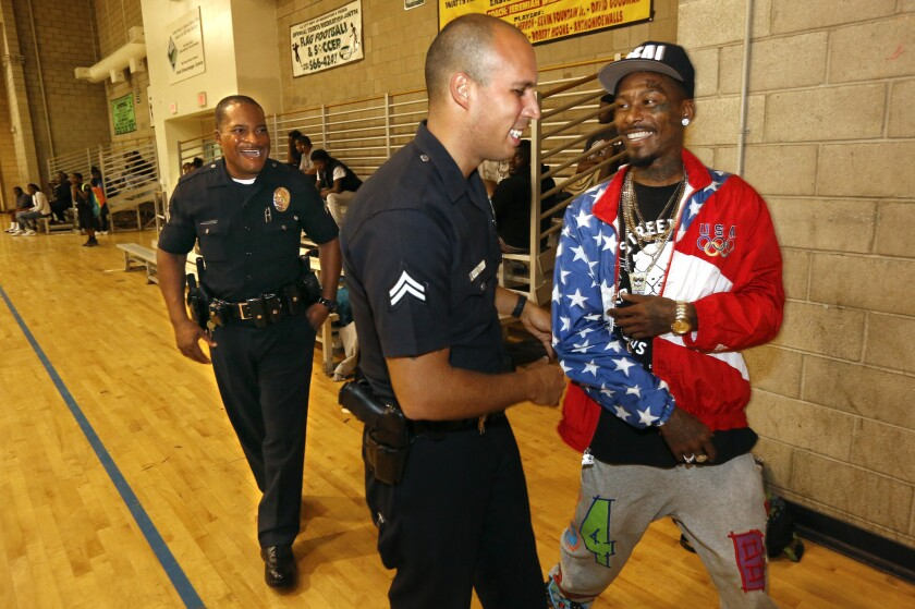 LAPD'sDelano Hutchins, left, and Angelo Marzan chat with Eric Romero in 2015 as part of the Community Safety Partnership.