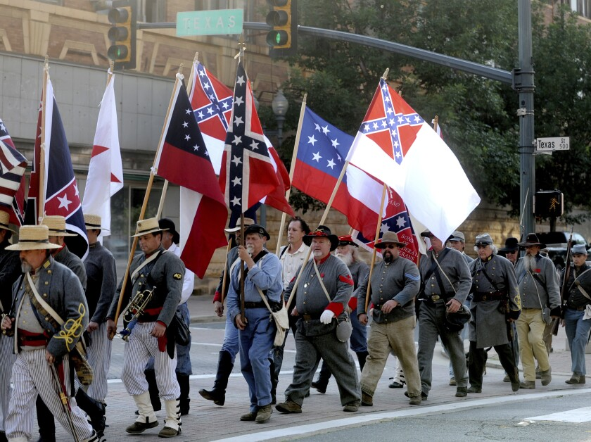 FILE - In this June 3, 2011 file photo, Sons of Confederate Veterans and others march through downtown Shreveport, La., on their way to commemorate Confederate Memorial Day near the Confederate flag and monument in front of Caddo Parish Courthouse. A federal appeals court was set to hear arguments Tuesday, Feb. 4, 2020, over a Louisiana city's decision to bar the Sons of Confederate Veterans from marching in a 2015 Christmas parade. Court records show the Louisiana Division of the group was denied permission to march in a parade in the city of Natchitoches that year amid concerns that many would be offended by the group carrying a Confederate flag. (Val Horvath Davidson/The Shreveport Times via AP, File)