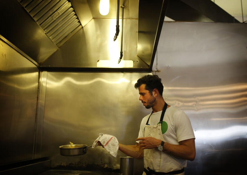 Ari Taymor cooks in the kitchen of Alma, his tiny downtown L.A. restaurant, which closed at the end of October.